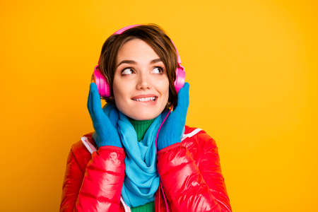 Closeup photo of pretty lady biting lip listen modern earphones looking interested empty space wear stylish casual red overcoat blue scarf gloves isolated yellow color background