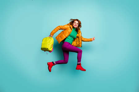 Full length photo of funny fast lady jump high rush home lessons classes finish carry school bag wear yellow coat scarf trousers turtleneck boots isolated teal color background Stock Photo