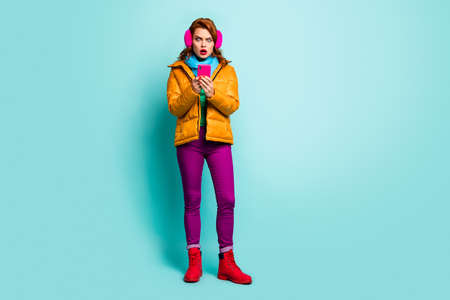 Oh no. Full size photo of traveler lady hold telephone open mouth read bad news wear trendy casual yellow overcoat scarf purple pants shoes isolated teal color background