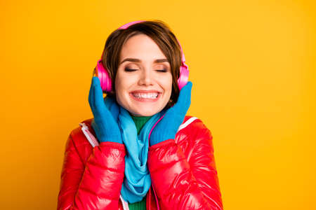 Closeup photo of beautiful lady eyes closed listen modern earphones romantic song words wear stylish casual red overcoat blue scarf gloves isolated yellow color background