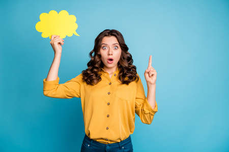 Portrait of her she nice attractive astonished wavy-haired girl holding in hands yellow copy space card pointing up isolated over bight vivid shine vibrant green blue turquoise color background