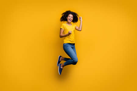 Full length body size view of her she nice attractive lovely cheerful cheery overjoyed crazy wavy-haired girl jumping celebrating isolated on bright vivid shine vibrant yellow color background 版權商用圖片