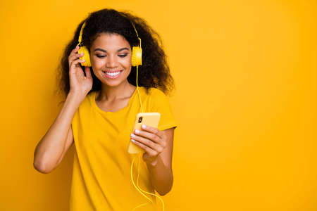 Close-up portrait of her she nice attractive charming cute cheerful cheery, wavy-haired girl listening stereo sound pop rock isolated over bright vivid shine vibrant yellow color background