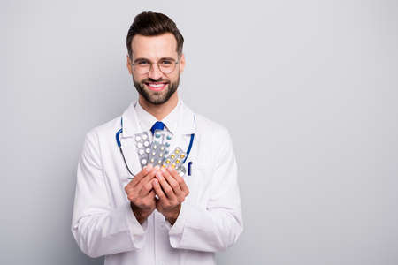 Close-up portrait of his he nice attractive glad cheerful cheery skilled professional doc holding in hands plates of tablets therapy solution isolated on light white gray pastel color background
