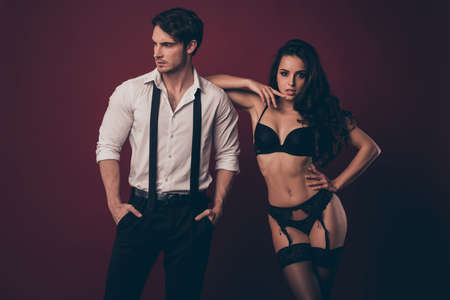 Photo of two sexy people husband nude wife stand close lean elbow shoulder start bdsm domination role play wear tuxedo suit lace boudoir pantyhose isolated burgundy color background Stock Photo
