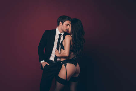 Profile photo of horny tender couple two people husband return home nude hot ass figure black underwear wife undress his office suit kissing isolated burgundy color background