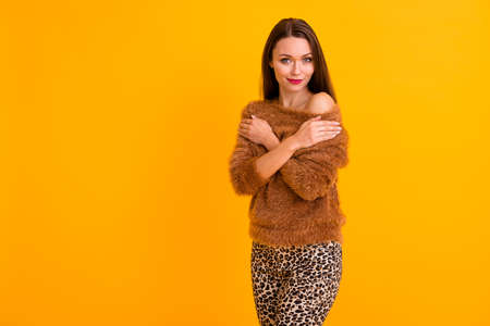 Photo of pretty tender lady hands hugging herself enjoy warmth soft pullover youth trend look wear fluffy open nude shoulder sweater leopard pants isolated yellow color background