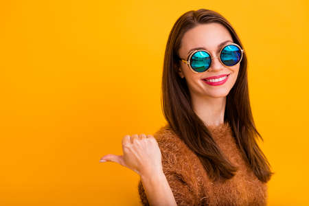 Photo of pretty toothy lady indicating thumb finger empty space offer low prices shopping center mall store wear sun specs fluffy artificial sweater isolated yellow color background