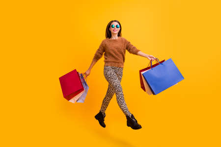Full body profile photo of pretty funny lady jumping high carry many packs excited shopper wear fluffy sweater leopard trousers footwear isolated yellow color background