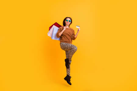 Full body photo of funny lady jump high carry packs shopaholic hold plastic credit card wear sun specs casual fluffy sweater leopard trousers boots isolated yellow color background