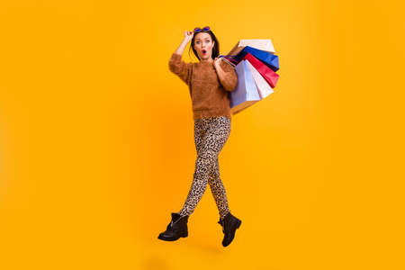 Full body profile photo of funny shocked lady jump high carry packs shopaholic open mouth new sales wear fluffy sweater leopard trousers boots isolated yellow color background