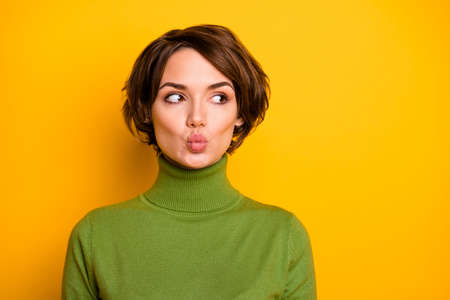 Closeup photo of pretty charming shy lady looking side empty space sending air kisses handsome guy wear casual green warm turtleneck isolated yellow color background