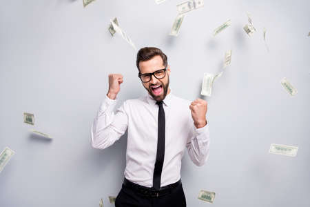 Successful delighted banker entrepreneur get benefit profit win lottery cashback money fall raise fists scream yes wear white shirt tie black pants trousers isolated grey color background