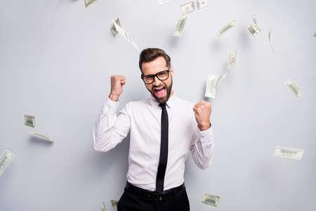 Un entrepreneur banquier ravi qui réussit tire profit des bénéfices de la loterie cashback argent chute lever les poings crier oui porter chemise blanche cravate pantalon noir pantalon isolé fond de couleur gris