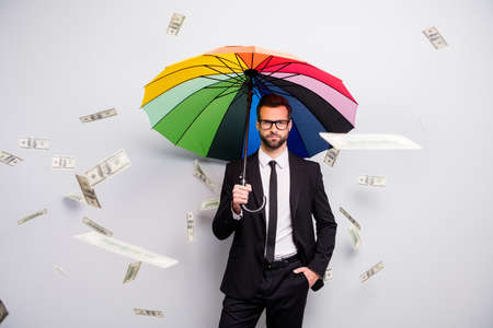 Serious investor manager go walk job hold colorful rainbow parasol shield casback rain money falling flying air wear black tux white shirt pants blazer jacket necktie isolated grey color background