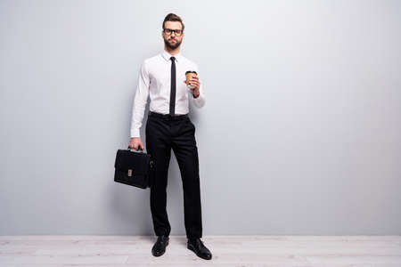 Full length photo confident cool smart agent marketer man hold mug latte beverage carry leather handbag need start-up conference wear white black outfit isolated grey color background