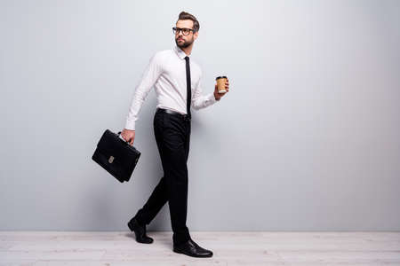 Full size profile side photo pensive company owner man go walk hold espresso cup leather handbag way briefing look copyspace wear white shirt black pants trousers isolated grey color background