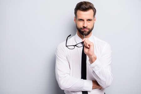 Porträt eines wunderschönen Freiberufler-Unternehmensinhabers, idealer Chef, der die Brille hält, sieht gut aus, bereit Entscheidungen zu treffen, die auf grauem Hintergrund isoliert sind Standard-Bild