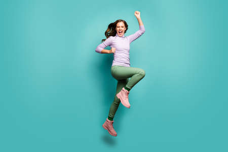 Full length photo of crazy lady jump high rejoicing black friday sales shopping center opening raise fists wear purple jumper green pants footwear isolated teal pastel color background