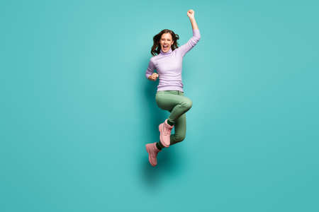 Full size photo of crazy beautiful lady jump high celebrate black friday sales shopping center opening raise fists wear purple jumper green pants footwear isolated teal pastel color background