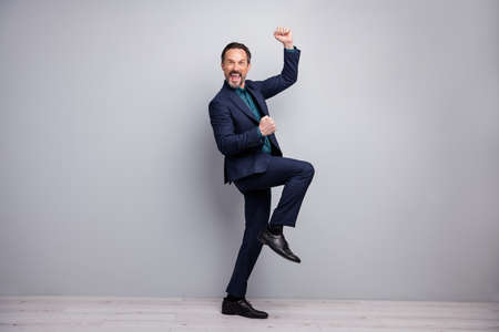 Yeah. Full length photo of crazy business mature man celebrating new startup investment raising fists yelling formalwear blazer shirt trousers blue suit isolated grey color background