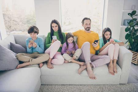 Ritratto di bel piede attraente grande famiglia pre-adolescente focalizzata completa bambini seduti sul divano utilizzando 5g app internet connessione wi-fi online navigazione navigando in casa in stile interno bianco chiaro Archivio Fotografico