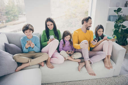 Portrait of nice attractive bare foot big full cheerful cheery family pre-teen kids spending free time sitting on sofa using 5g app internet online wi-fi connection at light white interior style house Stockfoto