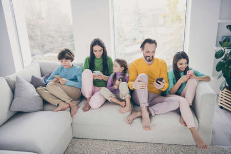 Portrait of nice attractive barefoot big full cheerful focused family pre-teen kids spending free time sitting on sofa using 5g app internet online at cozy comfortable light white interior style house