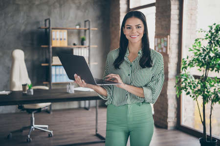Photo of attractive latin business lady hold notebook chatting colleagues read report meet partners friendly person wear striped shirt green pants stand modern interior office indoors