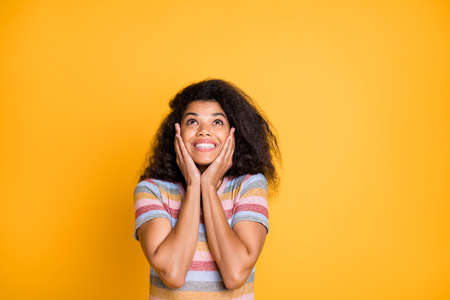Close-up portrait of her she nice attractive cheerful cheery girlish wavy-haired girl in striped tshirt looking up touching face wow isolated on bright vivid shine vibrant yellow color background Reklamní fotografie