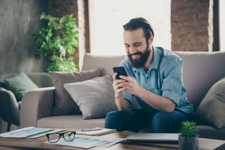 Portrait of his he nice attractive cheerful cheery brunet guy sitting on divan typing sms chatting with girlfriend at industrial loft modern style interior room house indoors