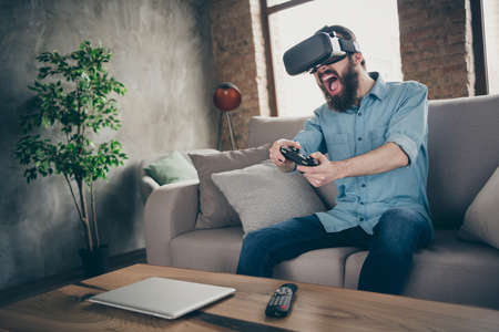 Portrait of his he nice attractive cheerful cheery crazy brunet guy sitting on divan wearing VR playing online game having fun at industrial loft modern style interior room house indoors