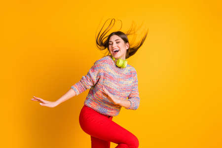 Portrait of positive cheerful funky girl listen music on head phones enjoy start dance dancing floor wear pullover red pants trousers isolated over shine color background Stock Photo