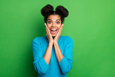 Photo of funny beautiful pretty dark skin lady arms on cheeks excited good mood beaming smile crazy facial expression wear blue turtleneck sweater isolated green color background