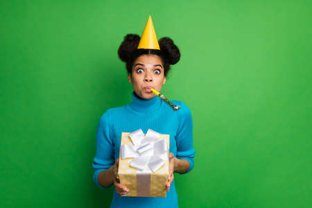 Photo of funky childish dark skin lady birthday hold big giftbox hands blowing noise maker in mouth wear paper cone hat blue turtleneck isolated green color background
