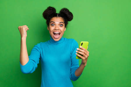 Photo of beautiful crazy dark skin lady hold telephone watch likes comments, reaction followers subscribers raise fist astonished wear blue turtleneck isolated green color background