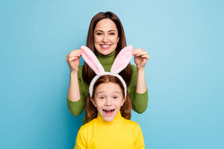 Portrait of nice attractive lovely funny charming pretty cheerful cheery, girls mom touching daughter's rabbit ears having fun isolated over bright vivid shine vibrant blue color background Imagens