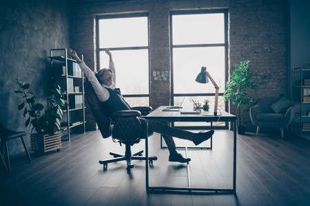 Profile side view of his he nice attractive classy chic gray-haired man economist top executive manager sitting in chair stretching at modern loft industrial style interior work place station indoors