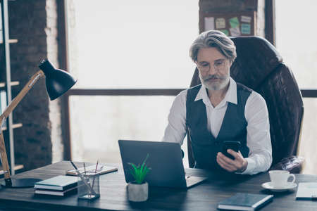 Smart confident old man executive white grey haired bearded investor sit table desk work laptop use smartphone have communication with clients wear vest waistcoat in workplace