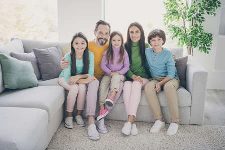 Full length photo of positive cheerful family three preteen kids schoolboy schoolgirl younger sister daddy mommy hug embrace sit couch chilling in house living room