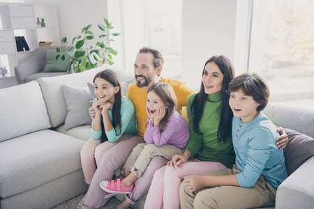 Excited crazy energetic family dad daddy mom mommy three small preteen kids schoolboy schoolgirl sit comfort couch watch incredible tv series amazed in house room
