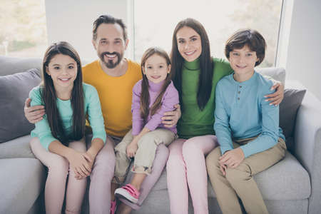 Positive loving cheerful ideal family concept. Mom daddy sit couch hug embrace her three children schoolboy schoolgirl in house living room Archivio Fotografico
