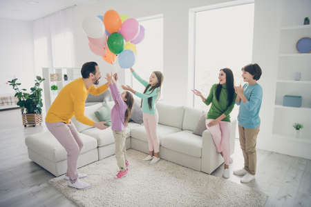 Full size photo of positive fun cheerful people family enjoy celebrating woman anniversary day launch many air baloons three little kids daddy mommy sit cozy couch in house Archivio Fotografico