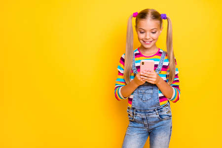 Portrait of positive cheerful kid use smart phone follow post share repost social network information wear jumper jeans isolated over bright color background