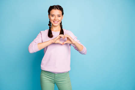 Portrait of her she nice attractive lovely cheerful cheery girlfriend showing heart gesture care isolated bright vivid shine vibrant blue green teal turquoise color background