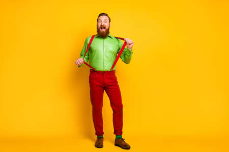 Full body photo of attractive funny guy model good mood playful macho wear green shirt red suspenders pants socks footwear isolated vibrant color background