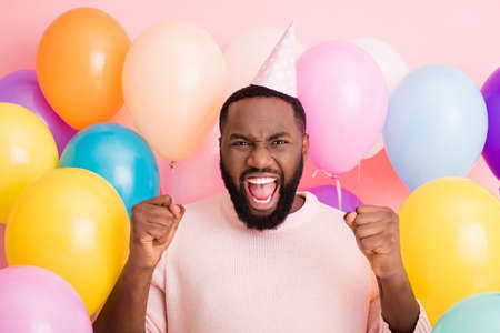 Photo of crazy funky dark skin guy enjoy birthday surprise raise fists surrounded many air balloons, rejoicing wear paper cone cap sweater on pink color background