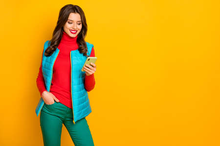 Portrait of positive cheerful cool girl use cell phone read comment repost post social network news wear green pants trousers isolated over yellow color background