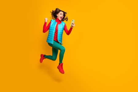 Full size photo delighted girl use smartphone follow social media autumn discount win lottery raise fists scream jump run wear green blue red pants shoes vest isolated yellow color background