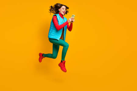 Full length profile side photo energetic crazy blogger girl jump use smartphone follow autumn season discount run wear red blue green pants trousers vest boots isolated bright color background
